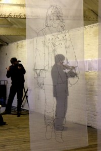 Playing Philip Glass's 'Strung Out', from the wall, seen through Rosie James's work
