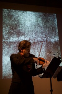 Peter Sheppard Skaerved with his drawing of the Thames. playing David Riebe's piece inspired by the art. Photo Neil Heyde