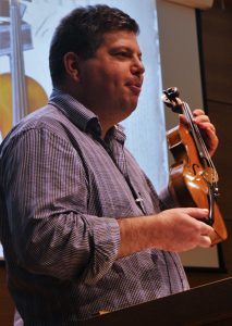 Ben Hebbert, talking about Stradivari and Enlightenment, holding a violin by Merlin